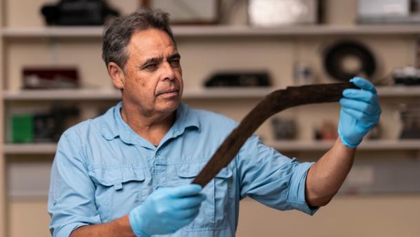 Dave Johnston, profesor de arqueología de la Universidad Nacional de Australia, analiza uno de los seis boomerangs descubiertos recientemente en Australia. (Jamie Kidston / Universidad Nacional de Australia)