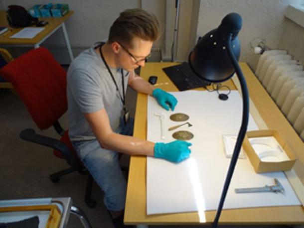 El Dr. Leszek Gardeła estudia un hacha en miniatura y joyas de una tumba de mujeres en Svingesaeter, Noruega. (Leszek Gardeła / Uso Justo)