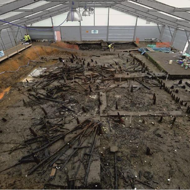 Excavación del asentamiento de viviendas apiladas Must Farm, que muestra el cuerpo principal del asentamiento colapsado (mirando hacia el este) en su matriz de sedimentos de río. (D. Webb)