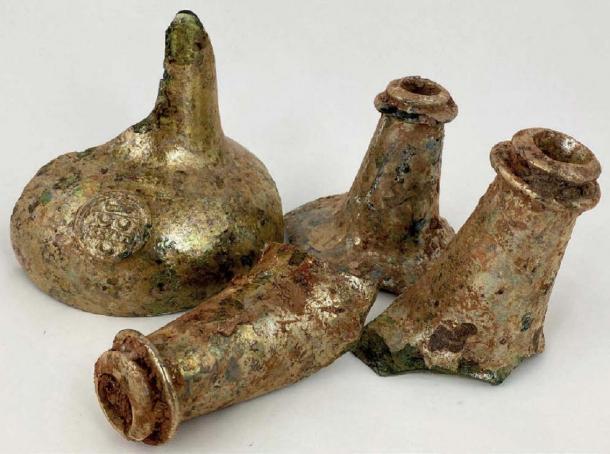 Este grupo de cuatro fragmentos de cuello, incluido uno con un sello, se encuentra con botellas de vino. (© BBR Auctions)