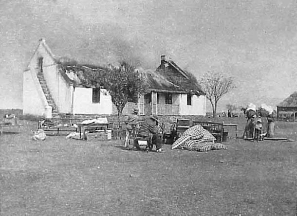 """Una respuesta británica a la guerra de guerrillas de los bóer fue una política de """"tierra quemada"""" para negar a la guerrilla suministros y refugio. En esta imagen, los civiles bóer observan cómo se quema su casa. (Dominio público)"""