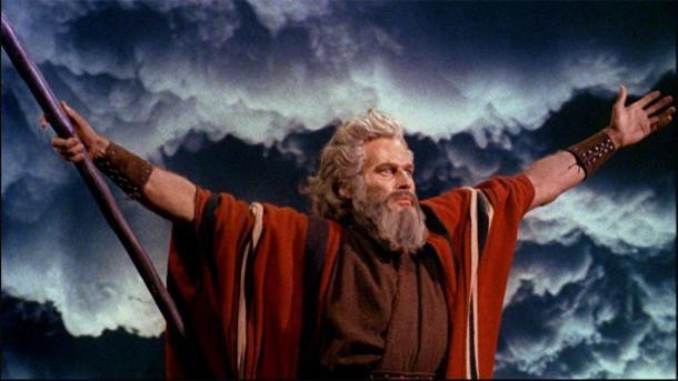 """Charlton Heston como Moisés en """"Los Diez Mandamientos"""" (1956), levantando los brazos mientras separa las aguas del Mar Rojo en una pose clásica de magos y sacerdotes egipcios. (Dominio publico)"""