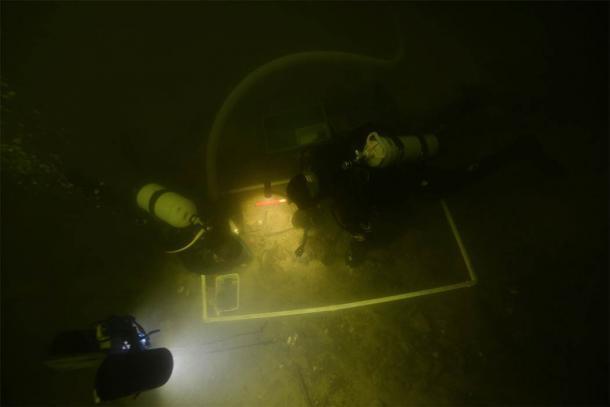 Arqueólogos submarinos que examinan los artefactos en el lago Asveja, Lituania. (G. Krakauskas)