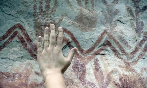 Esta imagen de un acantilado más bajo muestra huellas de manos de color rojo ocre y líneas geométricas. (Marie-Claire Thomas / Wild Blue Media Ltd)
