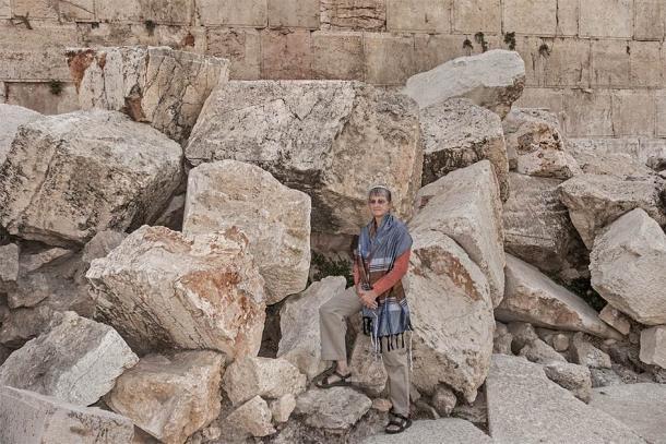 """Una rabina posando sobre las enormes piedras arrojadas desde el Monte del Templo por los romanos durante la Gran Revuelta Judía en Jerusalén, de donde fueron tomadas las piedras balistas """"malditas"""". (Sarit Richerson / Adobe Stock)"""