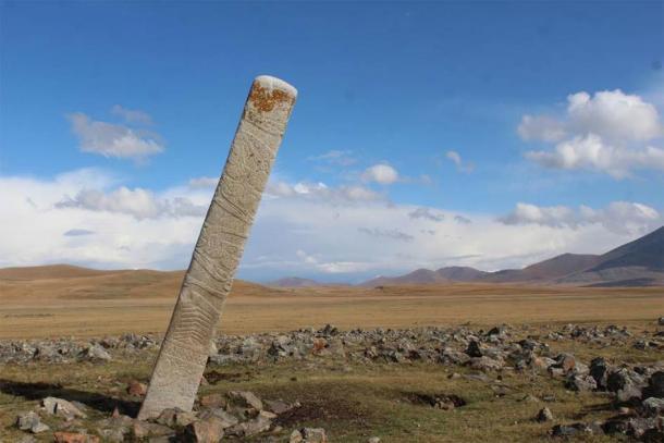 Una piedra de ciervo inclinada colocada frente a docenas de pequeños montículos de piedra que contienen entierros de caballos sacrificados ritualmente en el sitio del monumento de la Edad de Bronce de Ikh Tsagaanii Am, provincia de Bayankhongor, en el centro de Mongolia. (William Taylor)