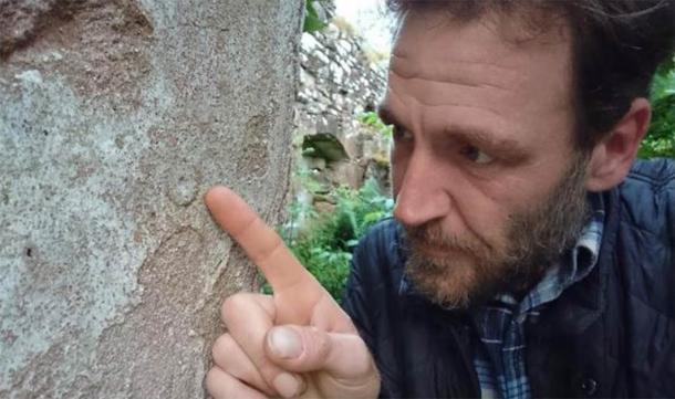 Ash inspecciona la marca de una bruja en el cementerio de Balnacoil que data de mediados del siglo XVIII. (Ashley Cowie)