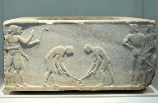 Base de un kouros funerario, encontrado en Kerameikos, construido en el muro de Themistokleian. Decorado con lo que parecen ser jugadores de un juego similar al hockey. (Zde / CC BY-SA 3.0 )