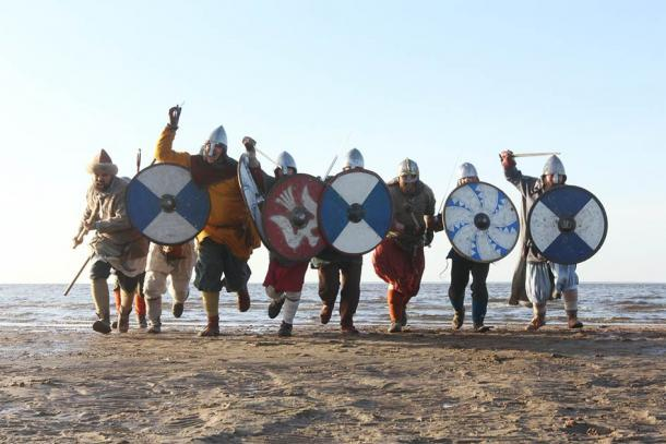 Representación de guerreros corriendo a la batalla usando armas vikingas y el típico escudo redondo. (destillat/ Adobe stock)