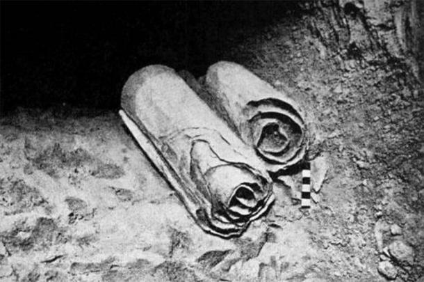 Dos rollos de los Rollos del Mar Muerto yacen en su ubicación en las Cuevas de Qumrán antes de ser retirados para que los arqueólogos los examinen académicamente. (Dominio público)