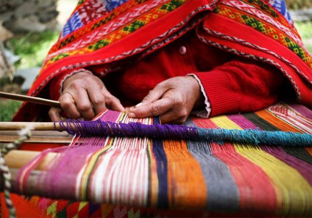 Cerca de una mujer indígena peruana tejiendo un textil tradicional cerca de Machu Picchu. (Shannon / Adobe Stock)