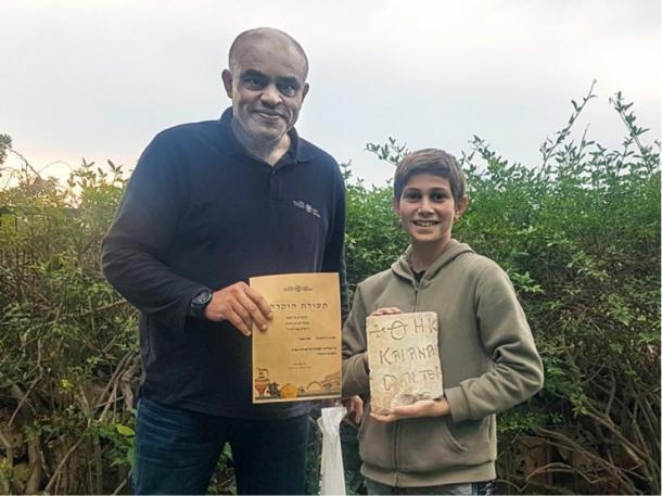 Karem Said, arqueólogo del distrito de Haifa en la IAA, otorga a Stav Meir un certificado de agradecimiento por su hallazgo de la inscripción bizantina de hace 1.500 años cerca de Cesarea. (Karem Said / Autoridad de Antigüedades de Israel)