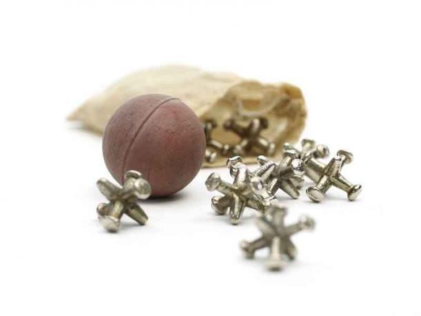 Los huesos de nudillos de metal se derramaron de una bolsa junto con la pelota que rebota: este es un juego de destreza y en la antigua Grecia en realidad usaban huesos de tobillo de oveja de forma similar. (Museo de los Niños de Indianápolis / CC BY-SA 3.0)