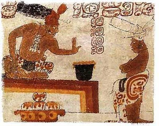 Un posible señor maya se sienta ante un individuo con un recipiente de chocolate espumoso. Dominio publico