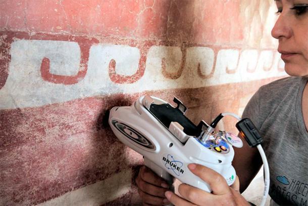 Un miembro del equipo interdisciplinario del INAH utiliza equipo especializado para identificar minerales de murales mesoamericanos previamente desconocidos en una pintura mural en el complejo Quetzalpapálotl. (Denisse Argote Espino / INAH)