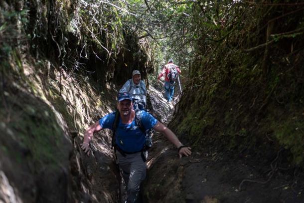 Miembros de la expedición trepan por un sendero de acceso a la montaña
