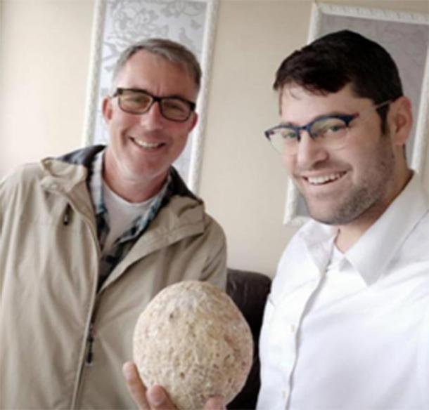 Moshe Manies (derecha) y Uzi Rotstein (izquierda) de la Autoridad de Antigüedades de Israel con la piedra ballesta robada. (Moshe Manies / IAA)