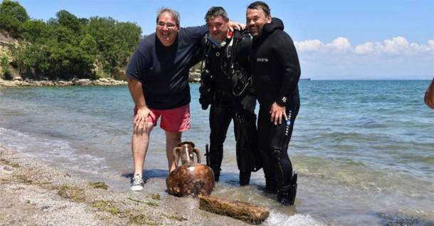 Investigadores entusiasmados posando con un ánfora perfecta y una piedra labrada encontrada bajo el agua, cerca de la costa del cabo Chiroza. (Municipio de Burgas)