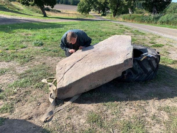 El runólogo Magnus Källström de la Junta del Patrimonio Nacional de Suecia estudia la piedra rúnica vikinga recién descubierta. (Ingemar Lundgren / Museo Västervik)