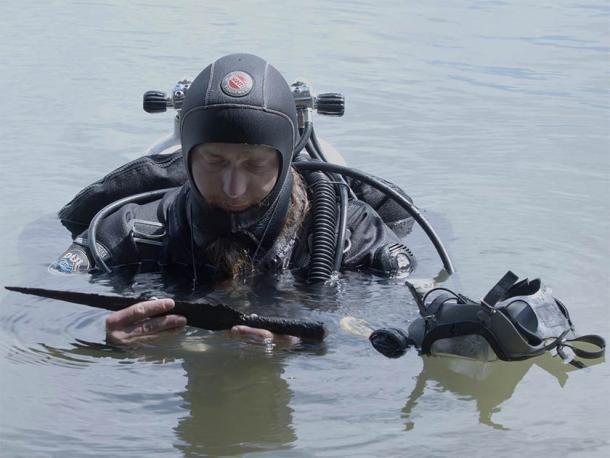Uno de los arqueólogos polacos apareció con solo uno de los 20 artefactos encontrados en el fondo del lago, incluida la rara espada medieval. (Universidad Nicolaus Copernicus)
