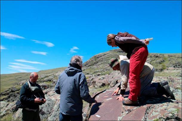 El equipo de arqueólogos inspeccionando el arte rupestre paleolítico en Kalgutinsky Rudnik, Rusia. (Hugues Plisson y Lidia Zotkina / Siberian Times)