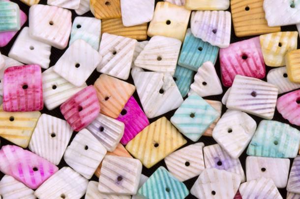 Las cáscaras de cowrie se hierven para resaltar su color y se perforan agujeros para ensartar. (Ogichobanov / Adobe)