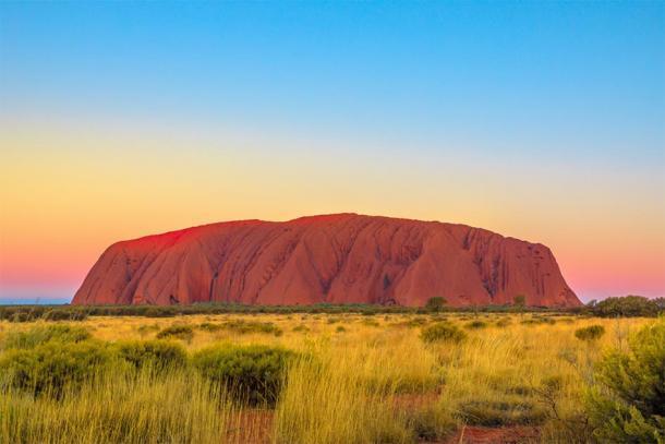 Foto de Uluru justo después del atardecer, donde se puede encontrar el arte rupestre aborigen. (bennymarty / Adobe Stock)