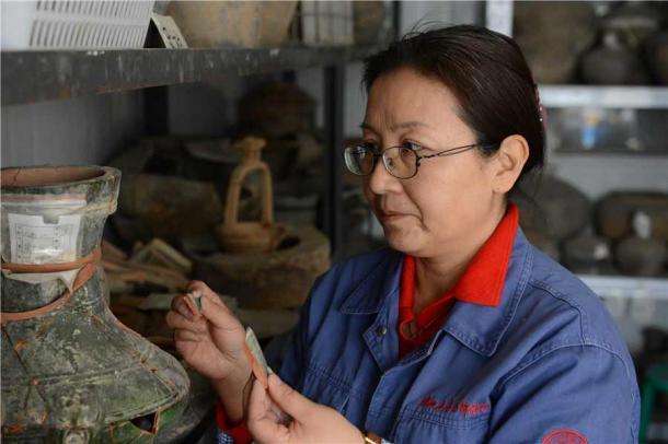 Xu Weihong trabajando en un jarrón encontrado en el antiguo sitio de Xianyang. (Zhang Xiping / China Daily)