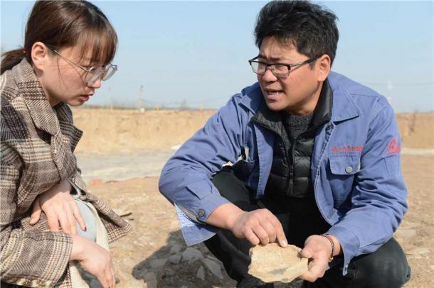 Zhang Yanglizheng, de la Academia de Arqueología de Shaanxi, a la derecha, y un trabajador de la oficina de reliquias local, examinan un mosaico encontrado en las ruinas. (Zhang Xiping / China Daily)