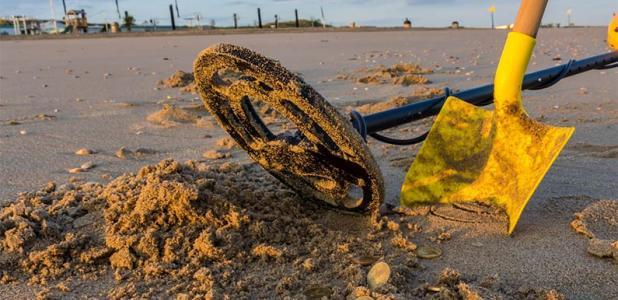 un detector de metales y una pala en la playa con monedas que podrían ser monedas medievales raras. ¡Nunca sabes!