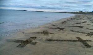 Fotografía de la playa irlandesa de Streedagh, llena de cruces dibujadas sobre su arena en homenaje a los caídos españoles de la Armada Invencible. (Fotografía: El Confidencial Digital)