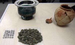 Portada-Las antiguas monedas romanas, datadas en el siglo I d. C. junto a la vasija de barro en la que se encontraban: el nombre del propietario está grabado sobre la superficie de la vasija. (Foto: BGNES)