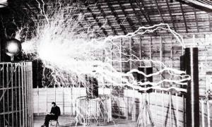 Portada - Fotografía de Nikola Tesla sentado en su laboratorio de Colorado Springs en diciembre de 1889 junto a su transmisor amplificador, en pleno funcionamiento. (Public Domain)