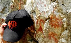 Portada - La imagen de una figura humana junto a un círculo – un signo solar, el símbolo del sol – se observa en la gorra de uno de los científicos. Sobre la roca se puede apreciar la pintura rupestre original. Fotografía: Sergei Alkin.