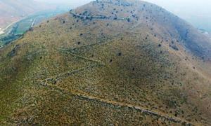 Portada - Restos de las murallas serpentean por la colina Strongilovoúni, lugar donde se ubicaba la antigua ciudad griega recientemente descubierta. (Fotografía: El País/SIA/EFAK/YPPOA)