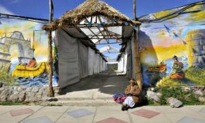 Portada - Mujer sentada en la ciudad peruana de Puno, a orillas del Lago Titicaca. (Fotografía: La Gran Época / Aizar Raldes / AFP / Getty Images)