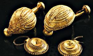 Portada - Tesoros de la cultura de Hallstatt: las fíbulas de bronce recubiertas de oro (longitud: 50 mm) y los colgantes (diámetro: 20 mm) hallados en la tumba del niño. (Fotografía: Antiquity/Cambridge Core)