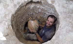 Portada - David Tanami, arqueólogo de la Autoridad de Antigüedades de Israel, se abre camino para extraer una vasija en la estrecha abertura de la tumba cananea ubicada cerca del Zoológico Bíblico de Jerusalén. (Shua Kisilevitz, Autoridad de Antigüedades de Israel)