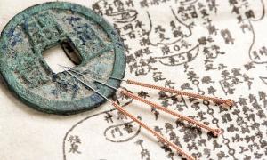un antiguo texto de anatomía chino y agujas de acupuntura.