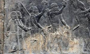 """Los soldados asirios llevan las cabezas decapitadas de sus prisioneros, como se muestra en una pared en el Palacio Sudoeste de Nínive, durante la """"Primera"""" Caída de Neneve"""