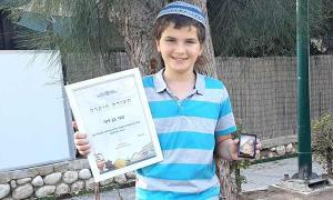 Zvi Ben-David, el niño que encontró el raro amuleto de la diosa de la fertilidad en el sur de Israel, con su certificado de reconocimiento de la IAA.