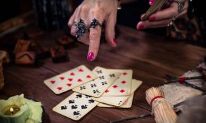 Adivina gitana predice el futuro con cartas. Adobe Stock / Alex Shevchenko