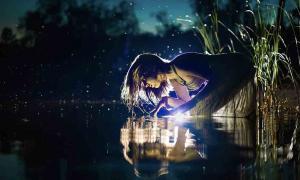 Una mujer mira fijamente a un lago oscuro. Crédito: diter / Adobe Stock