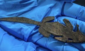 Fotografía de un arqueólogo que sostiene el ratón broma de cuero encontrado en el fuerte romano de Vindolanda. Fuente: Vindolanda Trust