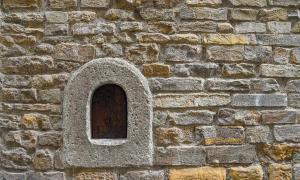 una vitrina de vino (buchetta del vino), utilizada en el pasado para vender vino directamente a los transeúntes, en el antiguo muro de piedra de un edificio antiguo en el centro histórico de Florencia, Toscana, Italia
