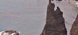"""Portada-Fotografía retrospectiva del roque llamado """"Dedo de Dios"""", localizado en Gran Canaria, España. A finales del 2005, los fuertes vientos de la tormenta tropical Delta ocasionaron el derrumbe y posterior hundimiento bajo el mar de su parte superior, de unos veinte metros de altura. Se trataba del rasgo más característico de este monumento natural, puesto que era el que venía a conformar el llamado 'dedo índice de Dios' que daba nombre a esta formación rocosa. (Public Domain)"""