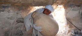 Portada - Un trabajador del Proyecto Tebano Imperio Medio saca una de las tinajas recientemente descubiertas entre un conjunto de elementos para el embalsamamiento de la tumba del visir Ipi, un alto funcionario del Imperio Medio que vivió hace más de 4.000 años. (Fotografía cortesía de la expedición española)