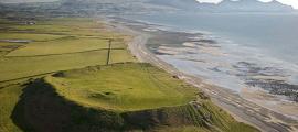 Una fotografía aérea del fuerte de la colina de la Edad de Hierro de Dinas Dinlle desde el norte (que sufre erosión costera); Gwynedd, Cymru / Gales. Cromlechs y sitios antiguos. (CADW / Visita Gales / CC BY SA 3.0)
