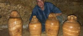 un arqueólogo egipcio posando con 4 de las vasijas canopicas encontradas en la tumba faraónica egipcia
