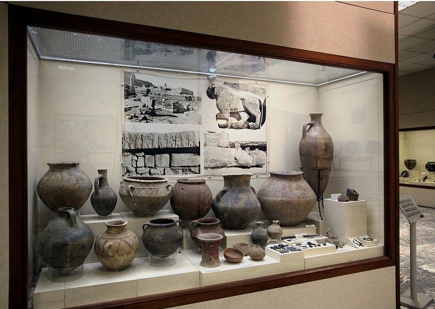 Cerámica y otros objetos diversos hallados en Aslantepe, Turquía, expuestos en la actualidad en el Museo Arqueológico de Malatya. Arriba a la derecha se puede observar la fotografía de uno de los leones de piedra. (CC BY-SA 3.0)